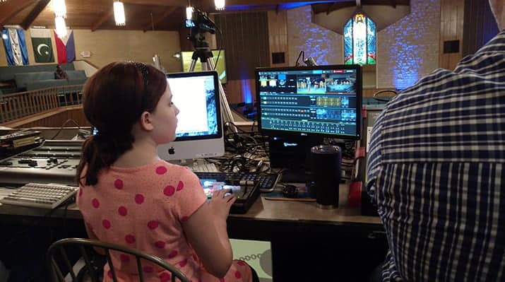 young girl sitting in front of video switcher being trained as a church volunteer