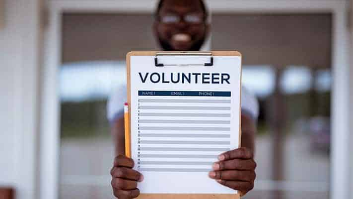 young man holding up a volunteer signup clipboard