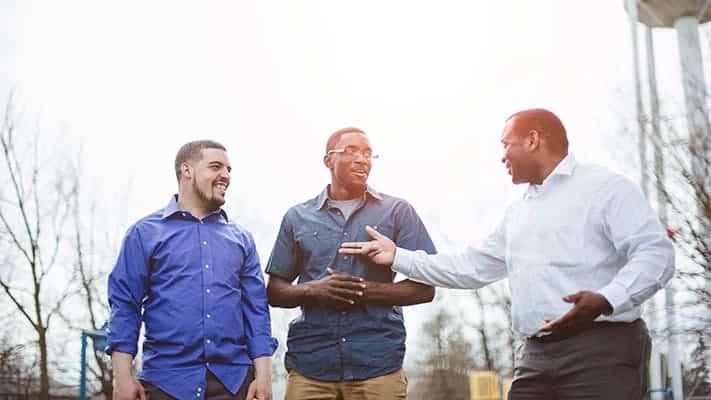 older gentlemen talking to two young men about volunteering in church