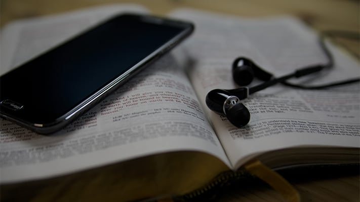 phone and headphones sitting on top of a bible